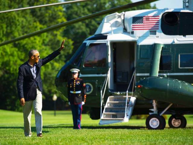 US President Barack Obama waves as he walks across the South Lawn of the White House
