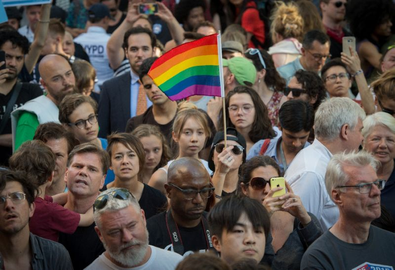 People wave flags during a vigil in reaction to the mass shooting at a gay nightclub