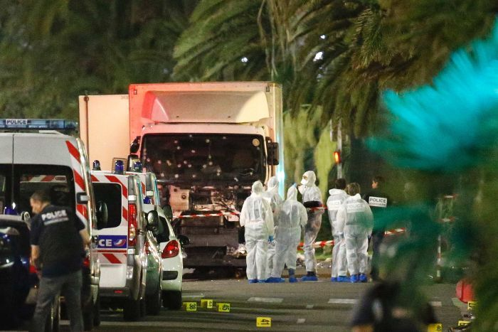 Police stand next to a truck that ran into a crowd celebrating Bastille Day