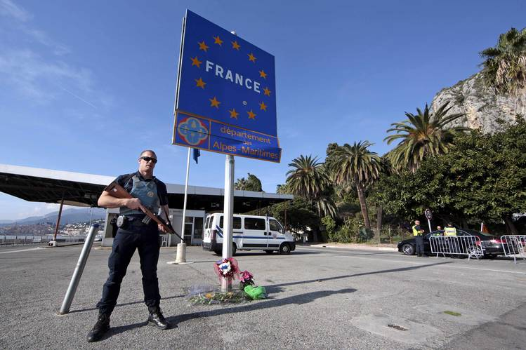 An armed French police officer stands guard at the Franco-Italian border to check vehicles