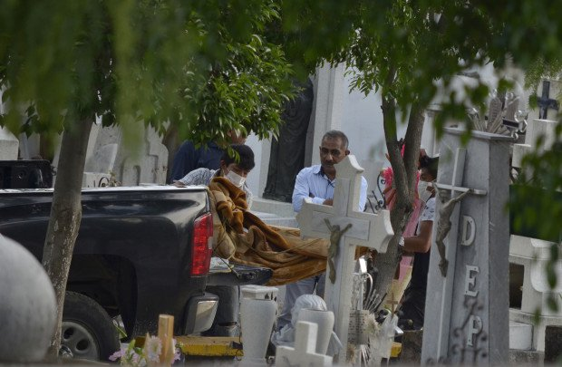 Forensic and cemetery workers unload the bodies of 11 slain family members