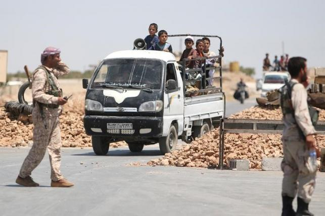 Syria Democratic Forces (SDF) fighters man a checkpoint as civilians on pick-up trucks evacuate from the southern districts of Manbij city after the SDF advanced into it in Aleppo Governorate, Syria