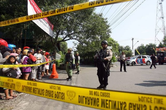 Indonesian police officers stand guard after a suicide bomb attack at the police headquarters in Solo