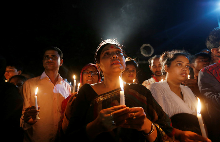 People attend a candlelight vigil for victims of the Dhaka attack in Bangladesh's capital