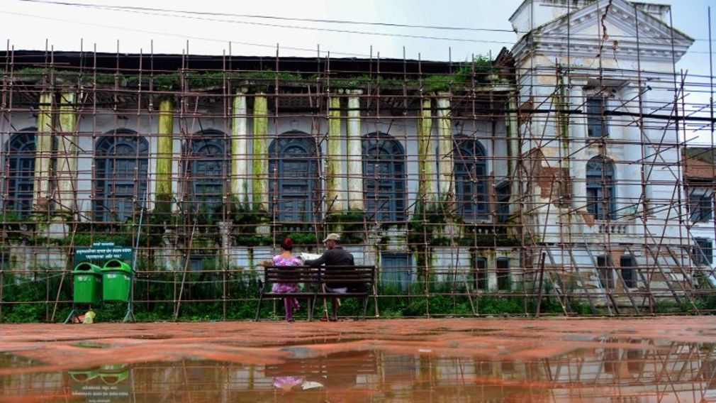 Nepali people sit on a bench in front of a royal palace covered by scaffolding as it undergoes repairs in Durbar Square in Kathmandu