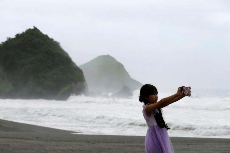 Waves are seen behind a girl as Typhoon Nepartak approaches, in Yilan, Taiwan
