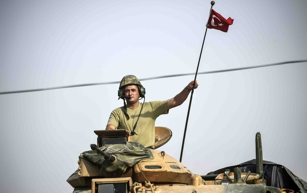 A soldier gesturing as Turkish Army tanks drive to the Syrian Turkish border town of Jarabulus