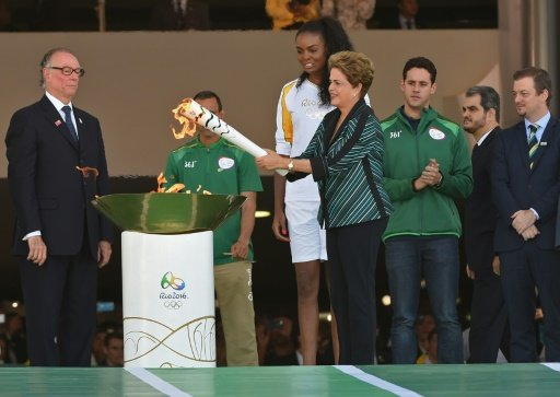 Brazilian President Dilma Rousseff lights the Olympic torch at Planalto Palace in Brasilia following the flame's arrival from Geneva