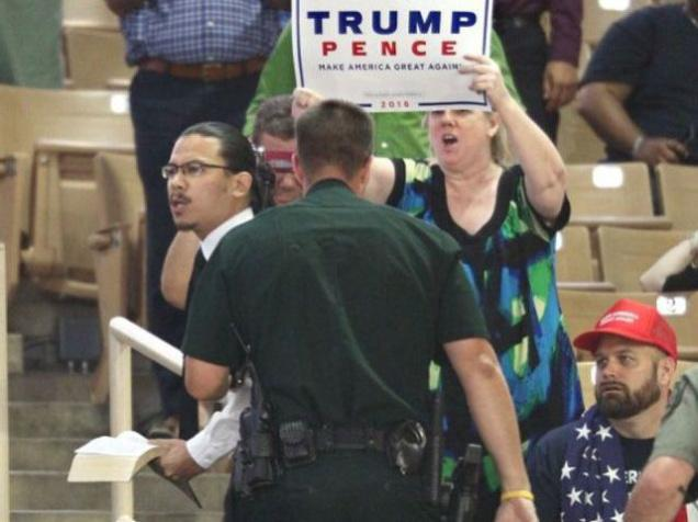 A protester holding and quoting from a Bible is hustled away by security after interrupting a campaign rally of Republican presidential candidate Donald Trump (not seen) at Silver Spurs Arena, inside the Osceola Heritage Park in Kissimmee, Florida on Thursday
