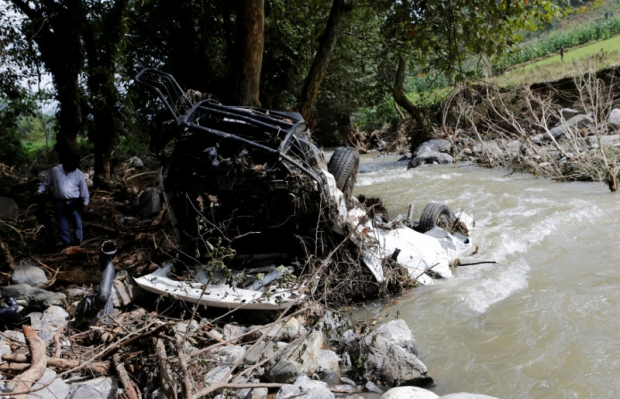 a destroyed car on the river after a mudslide in the town of Cuacuila, caused by Tropical Storm Earl over the weekend in the state of Puebla, Mexico