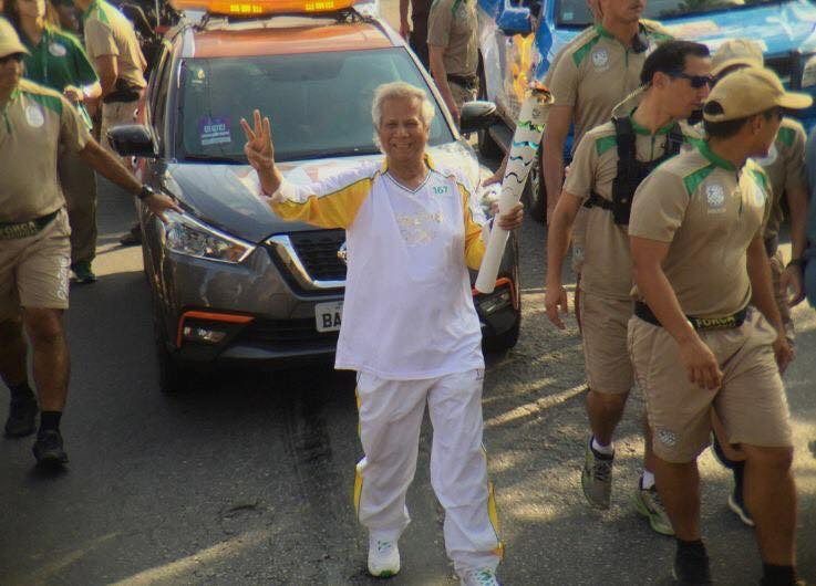 Nobel Laureate Professor Muhammad Yunus flanked by volunteers carrying the Olympic Torch in Rio.