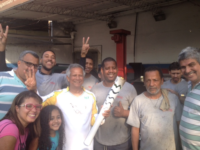Nobel Laureate Professor Muhammad Yunus with Olympic torch posing for a photo with a group of local spectators during his Torch Relay through the poor neighborhoods of Rio.