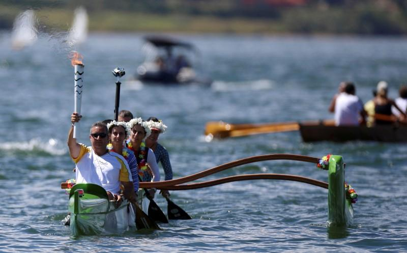 Canoeist Rubens Pompeu takes part in the Olympic Flame torch relay at Paranoa lake in Brasilia, Brazil, May 3, 2016. REUTERS/Adriano Machado