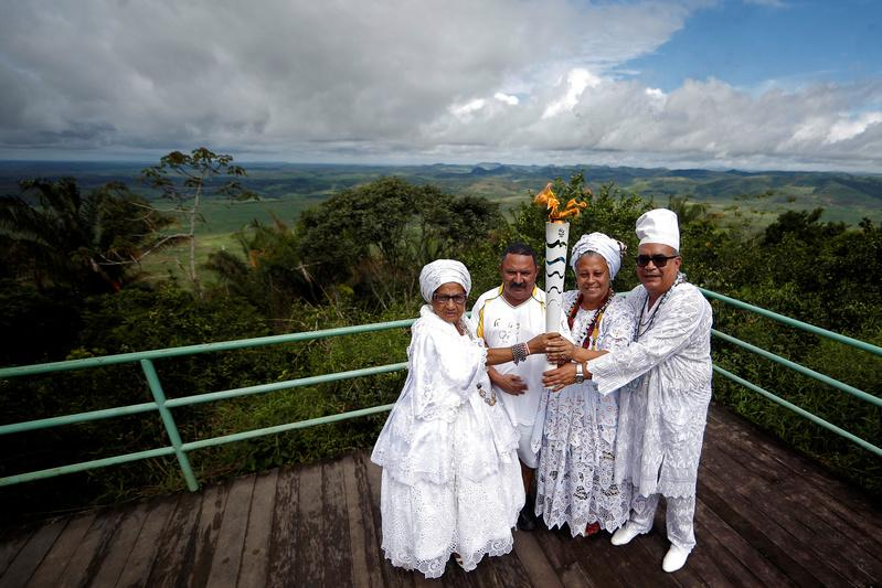Resident Francisco Neto (2nd L) takes part in the Olympic Flame torch relay at mountain range Serra da Barriga in Uniao dos Palmares, Alagoas state, Brazil, May 30, 2016. Fernando Soutello/Courtesy of Rio2016/Handout via Reuters