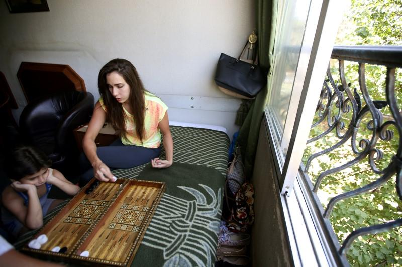 Syrian swimmer Baean Jouma (R) plays backgammon with her mother inside her hotel room in Damascus, Syria. *PHOTOs:REUTERS