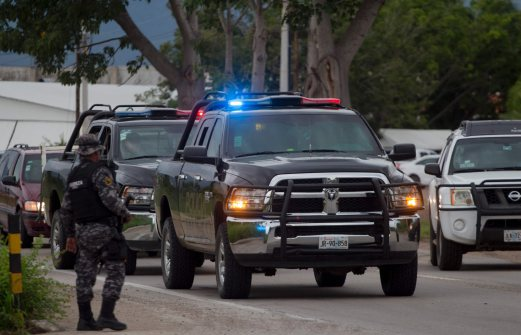 """Jalisco state police patrol the streets during a security operation in Puerto Vallarta in Mexico's western state of Jalisco on August 17, 2016. Jesus Alfredo Guzman Salazar, the son of drug lord Joaquin """"El Chapo"""" Guzman, was among a group kidnapped from a bar in the Mexican resort city of Puerto Vallarta, authorities confirmed Tuesday. Seven gunmen in pickup trucks swooped down on the upscale bar and restaurant Monday around dawn and abducted the victims. Investigators said it was likely part of a settling of scores between rival drug cartels. / AFP PHOTO / HECTOR GUERRERO"""