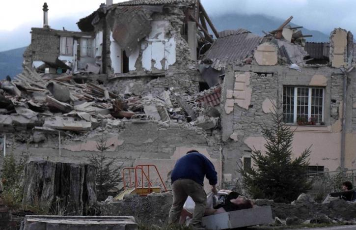 A man helps a woman in front of a collapsed building following an earthquake in Amatrice, central Italy, August 24, 2016.  REUTERS/Emiliano Grillotti