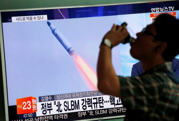 A passenger walks past a TV screen broadcasting a news report on North Korea's submarine-launched ballistic missile fired from North Korea's east coast port of Sinpo, at a railway station in Seoul, South Korea, August 24, 2016  REUTERS/Kim Hong-Ji