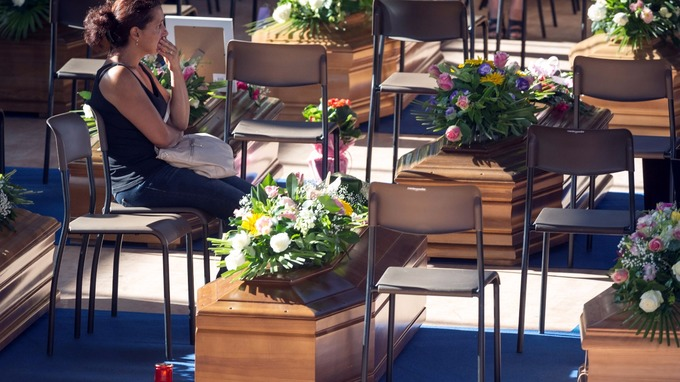 A woman sits next to a coffin to pay her respects as she attends a funeral for the earthquake victims