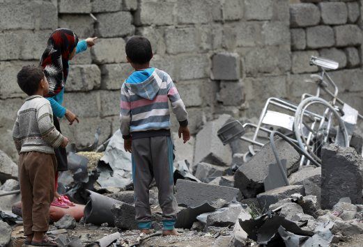 Yemeni children stand amidst the rubble of a house in Yemen's Huthi rebel-held capital Sanaa on August 11, 2016