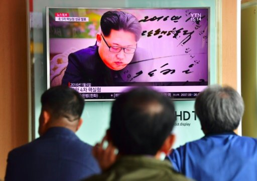 People watch a TV broadcast, showing file footage of North Korean leader Kim Jong-Un, at a railway station in Seoul