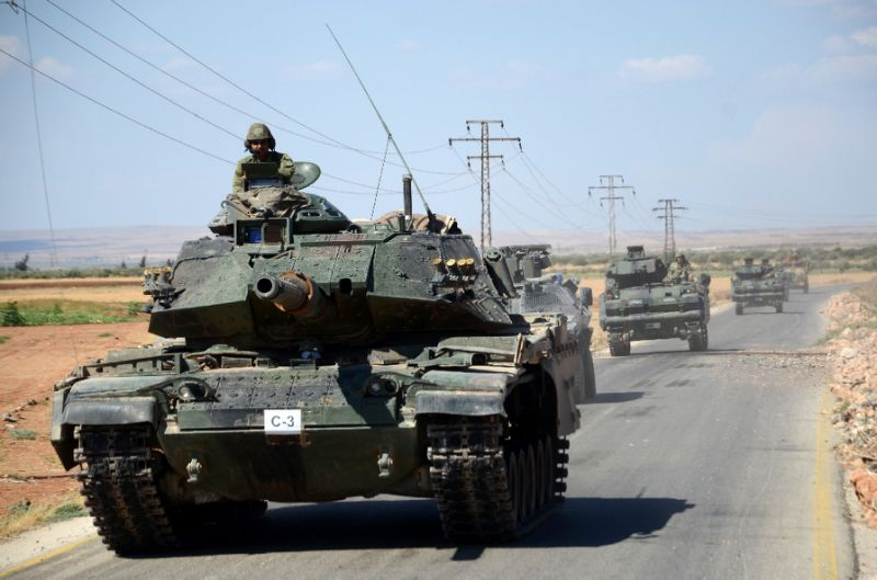 Turkish tanks move along a road near the Syrian village of al-Waqf