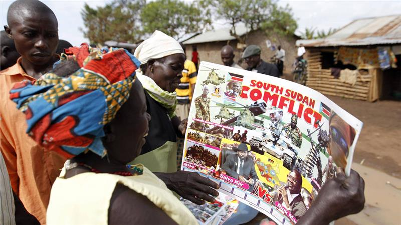 Refugees from South Sudan look at a photo montage depicting the conflict in their country on a calendar