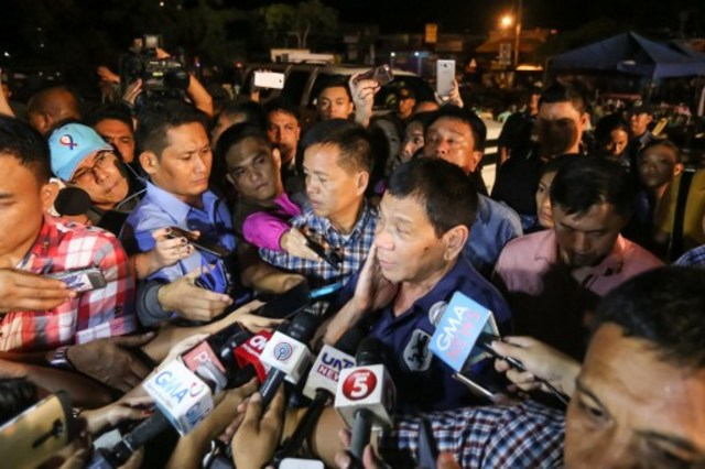 Philippine President Rodrigo Duterte speaks to members of the media as he visits the site of an explosion at a nigth market in Davao City in southern island of Mindanao early September 3, 2016.  At least 10 people died and dozens were injured when an explosion rocked Duterte's home city of Davao on September 2, 2016 night