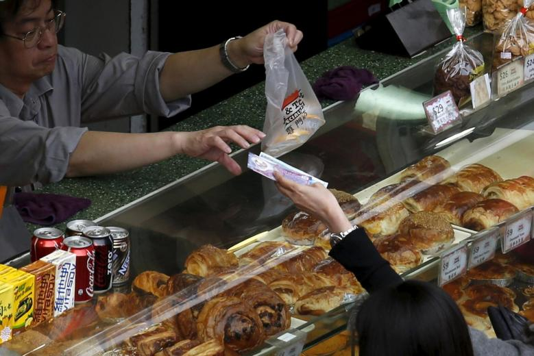 A worker receives money from a consumer at a bread store, the day Hong Kong government releases its latest consumer price index (CPI) figures in Hong Kong