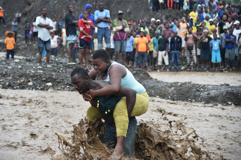 A man carries a woman across a river at Petit Goave where a bridge collapsed during the rains of the Hurricane Matthew, southwest of Port-au-Prince