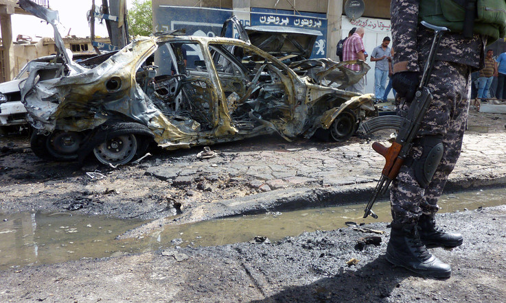 An Iraqi soldier stands on the scene of a car bombing on 30 May 2013 in Baghdad