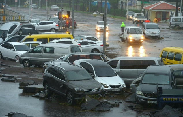 Cars damaged by flood waters caused by Typhoon Chaba are seen along a street in the southern island of Jeju on October 5, 2016