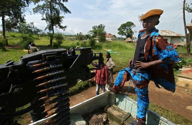 A Union of Congolese Patriots child fighter stands by a machine gun fixed on a pickup at a military camp in Bunia, northeastern Democratic Republic of Congo in 2003