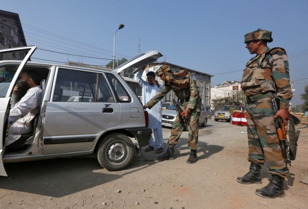 An Indian army soldier searches the boot of a car at a temporary check point near their headquarters in Srinagar