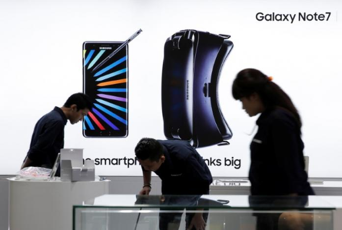 Sales promotion staff stand in front of a Galaxy Note 7 advertisement at a Samsung store in Jakarta, Indonesia