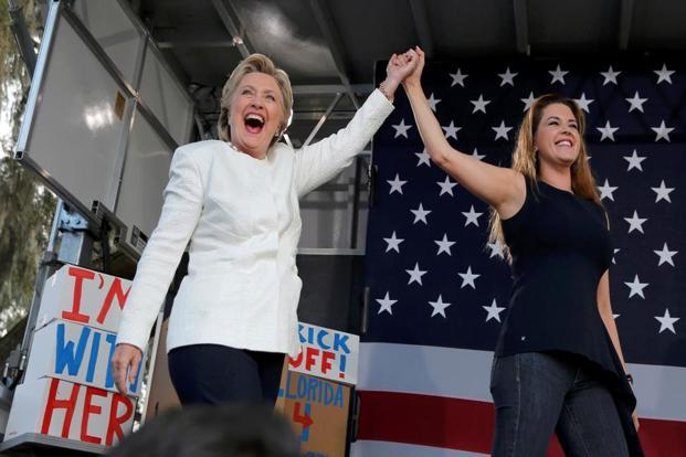 Democratic US presidential nominee Hillary Clinton (L) takes the stage with Alicia Machado after being introduced at an 'early voting' campaign rally in Florida