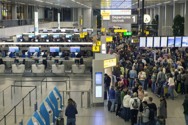 File picture shows travellers queuing at the departure zone of the Amsterdam Airport Schiphol. Dutch police launched a sweep at the Rotterdam airport today after receiving a tip-off about a possible terror threat