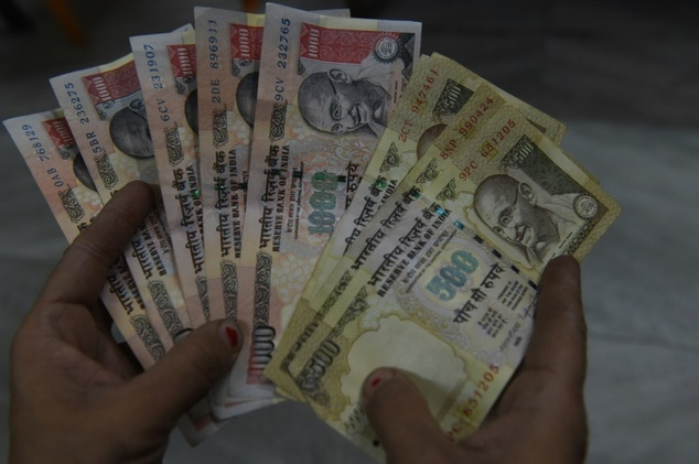 An Indian resident holds 500 and 1000 rupee banknotes in New Delhi