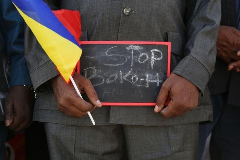 "A man holds a sign that reads ""Stop Boko Haram"" at a rally to support Chadian troops heading to Cameroon to fight Boko Haram, in Ndjamena"