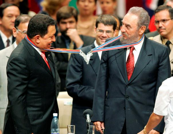 Venezuela's President Hugo Chavez (L) and his Cuban counterpart Fidel Castro joke after joining their medallions, given by medical graduates, at Havana's Karl Marx theatre, in August 20, 2005