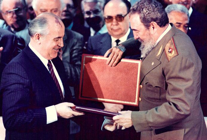 Then Cuban President Fidel Castro (R) and then Soviet leader Mikhail Gorbachev (L) exchange documents during a treaty signing ceremony in Havana on April 4, 1989