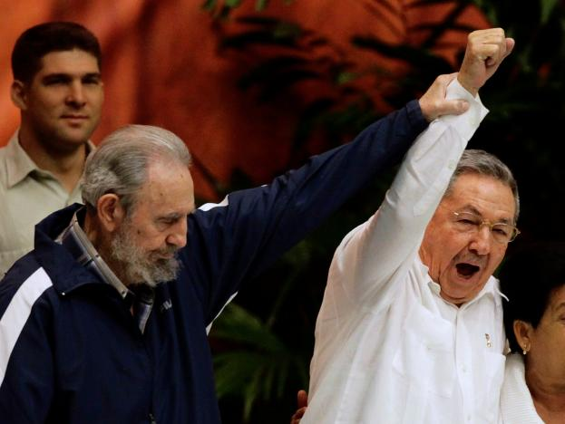 Former Cuban leader Fidel Castro (L) holds up the arm of his brother, Cuba's President Raul Castro, during the closing ceremony of the sixth Cuban Communist Party (PCC) congress in Havana