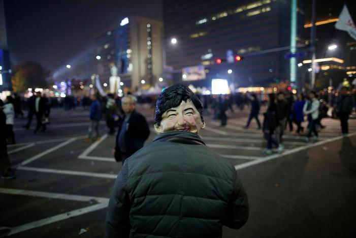 A man wearing a mask depicting South Korean President Park Geun-hye watches South Koreans take part in a rally calling on embattled Park to resign over a growing influence-peddling scandal in central Seoul, South Korea