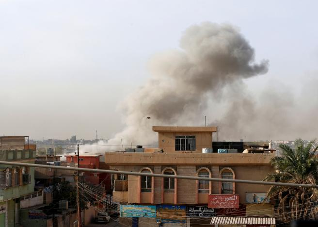 Smoke rises from an area controlled by the Islamic State after a member of the Iraqi Counter Terrorism Service fires mortars during a fight with Islamic State militants in the al-Zahraa neighborhood of Mosul, Iraq