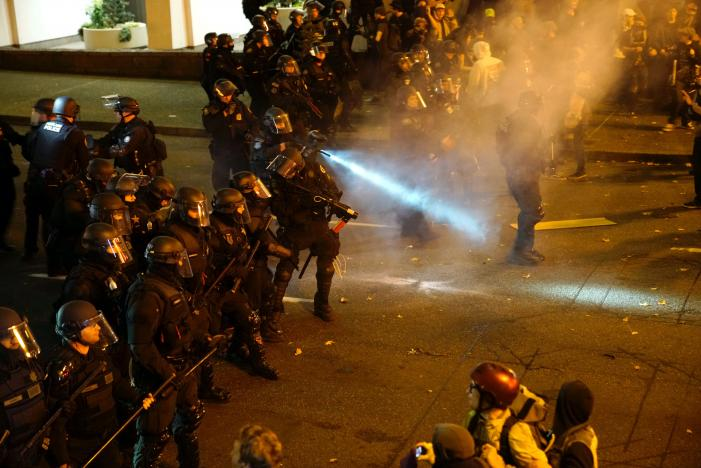 A police officer sprays the crowd with an irritant during a protest against the election of Republican Donald Trump as President of the United States in Portland, Oregon, U.S.
